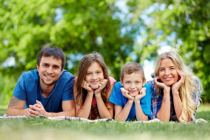 Photo of happy family of four lying on grass during summer rest