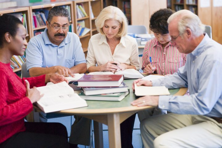 Group of adults around a table stacked with books
